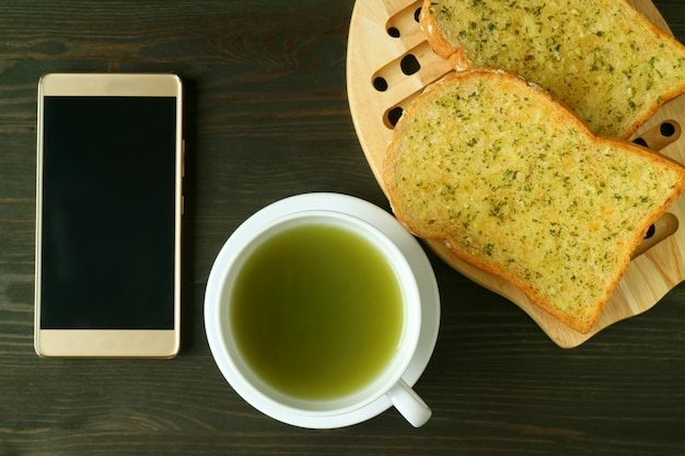 Empty screen smartphone with a cup of green tea and garlic butter toasts on dark