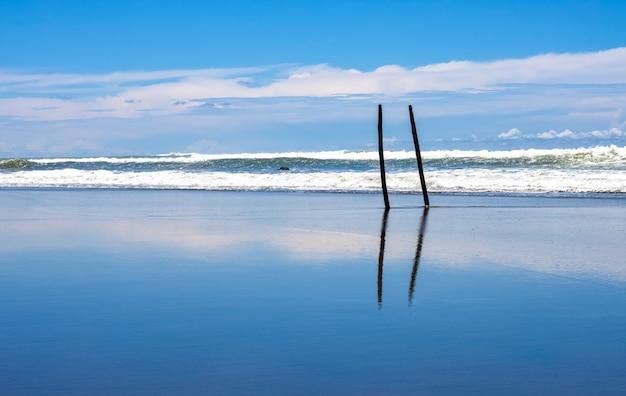 하늘 반사와 거친 파도와 깨끗한 하늘 아래 빈 바다 해변