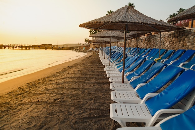 Empty sea beach with a flat row of sun beds and umbrellas at sunrise