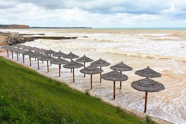 嵐の間に傘が水で溢れた空の海のビーチホリデーシーズンの終わり