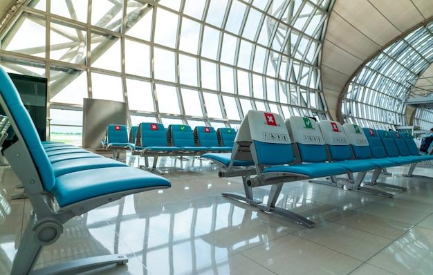 空港ターミナルの出発ラウンジの空席。安全のためにコロナウイルスと乗客の社会的距離を保護するために、1つの座席の距離を維持します。障害者のための優先席