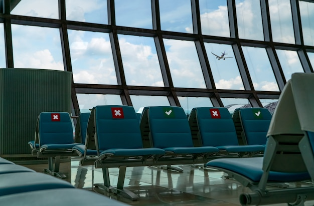 Свободное место в зале вылета терминала аэропорта. расстояние для одного места соблюдайте дистанцию, чтобы защитить коронавирус, и социальное дистанцирование пассажиров в целях безопасности. виден самолет, летящий через стеклянное окно.