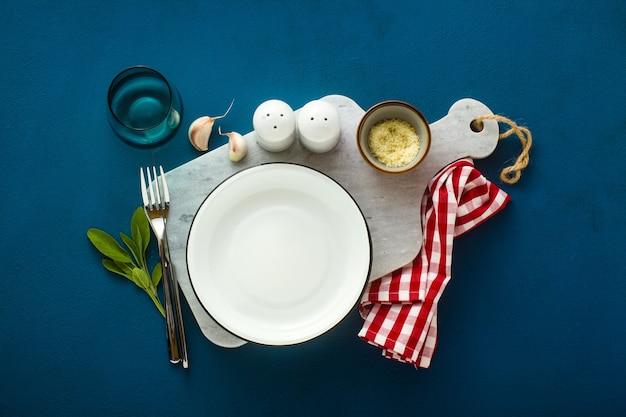 Пустая тарелка на мраморной сервировочной доске и фоне голубых специй
