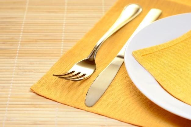 Пустой сервированный стол в ресторане с желтой скатертью