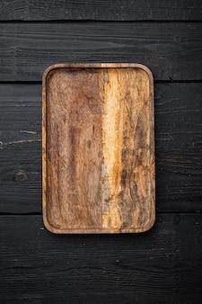 Набор пустых сервировочных досок, плоская планировка, вид сверху, с копией пространства для текста или вашего продукта, на черном фоне деревянного стола