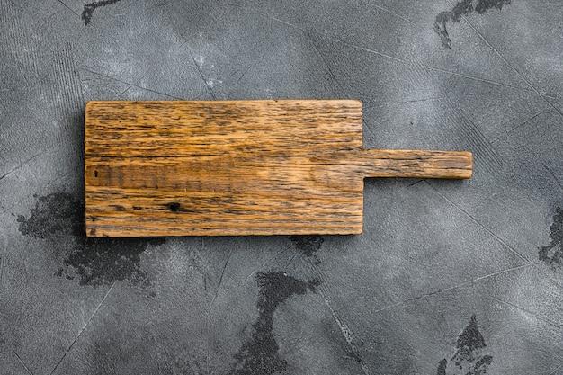 Набор пустых сервировочных досок, плоская планировка, вид сверху, с копией пространства для текста или вашего продукта, на фоне серого каменного стола