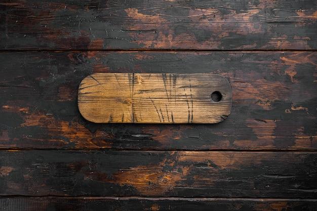 Набор пустых сервировочных досок, плоская планировка, вид сверху, с копией пространства для текста или вашего продукта, на фоне старого темного деревянного стола