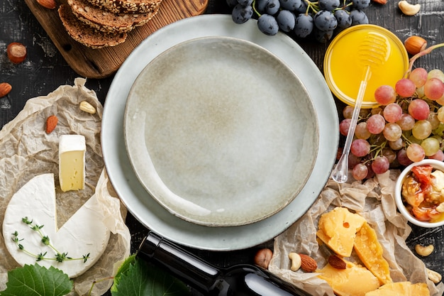Пустая сервировочная тарелка в центральной рамке из меда, винограда, сыров, закусок, других пищевых ингредиентов, гастрономических закусок. копируйте пространство копии или шаблон на синей пластине. вид сверху керамическое блюдо.