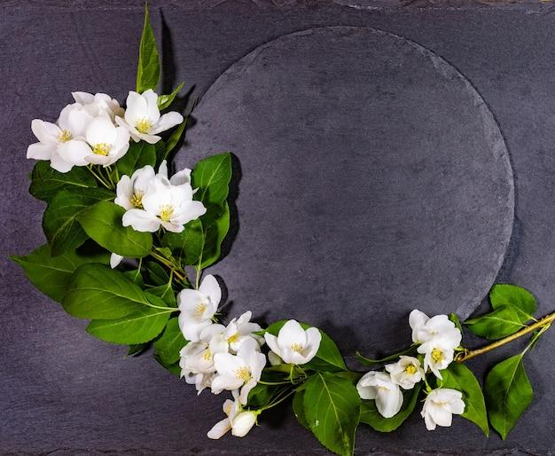 빈 셰일 라운드 블랙 서빙 보드 흰색 사과 나무 나뭇 가지와 함께 서빙 또는 봄 휴가에 요리법에 대한 축제 모형으로. 상위 뷰, 복사 공간.