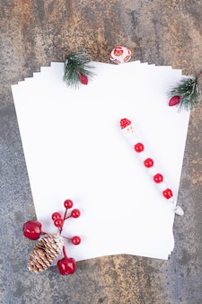 Fogli vuoti di carta con decorazioni natalizie sulla superficie in marmo