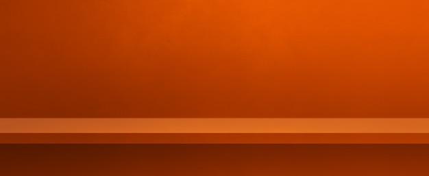 オレンジ色の壁に空の棚。背景テンプレートシーン。横バナー
