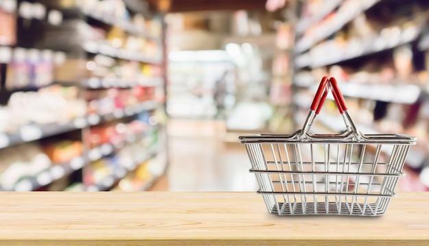 食料品店のスーパーマーケットの木製のテーブルに空のショッピングバスケットは、背景をぼかし