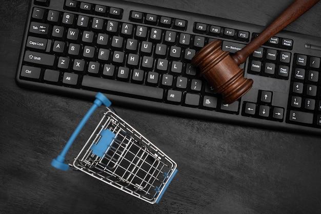 空のショッピングカートと裁判官がキーボードを叩きます。オンラインオークション。