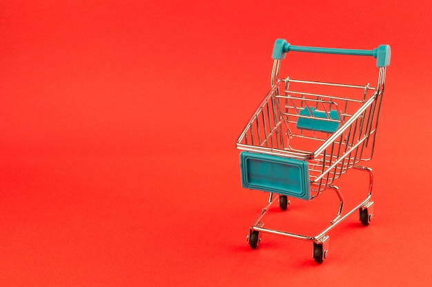 Empty shopping cart on bright red background