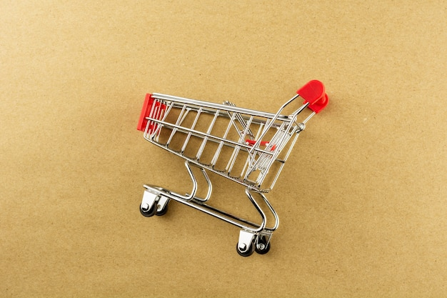 Empty shopping cart on brown paper background.