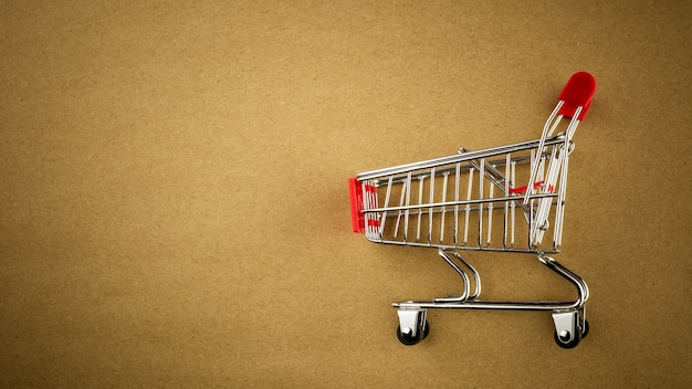 Empty shopping cart on brown paper background