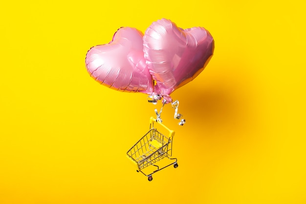 Empty shopping cart flies on pink heart shaped balloons on yellow background.