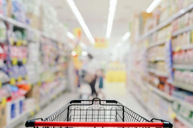スーパーマーケットの背景をぼかした写真の空のショッピングカート