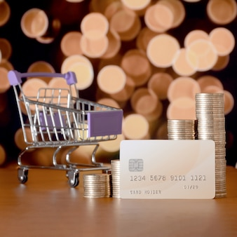 Empty shopping cart and money stacks in growth graph at the beige credit card