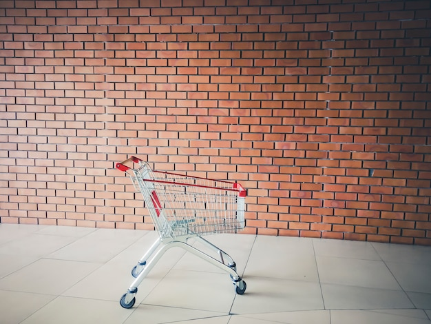Empty shopping cart near brick wall . shopping supermarket cart. shopping time concept