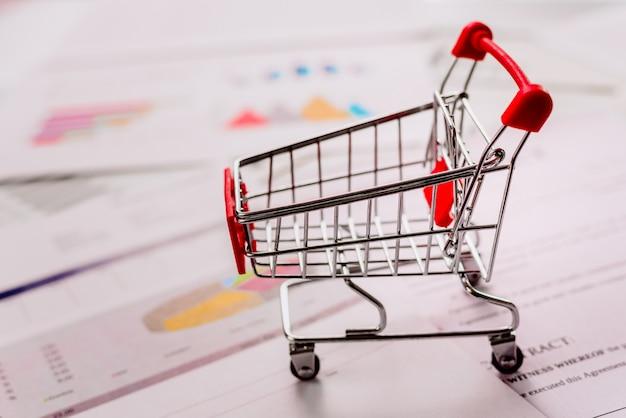 グラフィックスと経済データを含むドキュメントの空のショッピングカート、デフォーカス