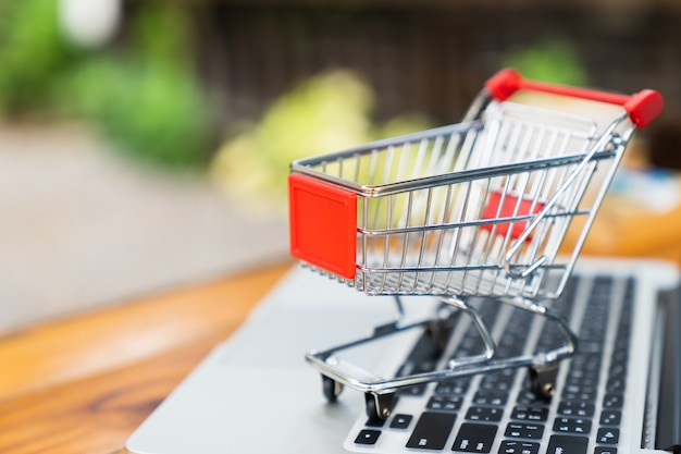 Empty shopping cart on table with laptop keyboard and copy space for online shopping concept