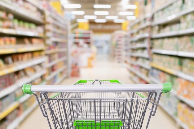抽象ぼかしスーパーマーケットのディスカウントストアの通路と製品棚のインテリアの焦点がぼけた背景を持つ空のショッピングカート