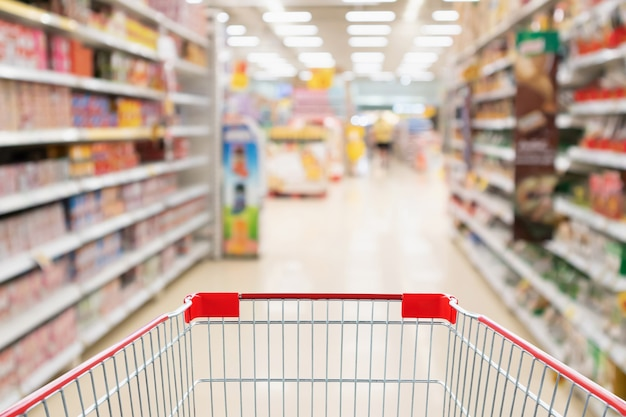 抽象ぼかしスーパーマーケットディスカウントストアの通路と製品棚のインテリアの焦点がぼけた背景を持つ空のショッピングカート