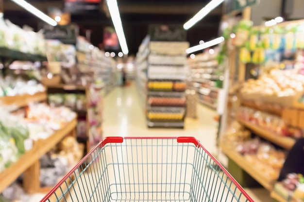 Empty shopping cart with abstract supermarket grocery store blurred defocused background with bokeh light