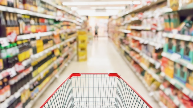 スーパーマーケットの棚の通路の内部が焦点がぼけた背景をぼかす空のショッピングカート