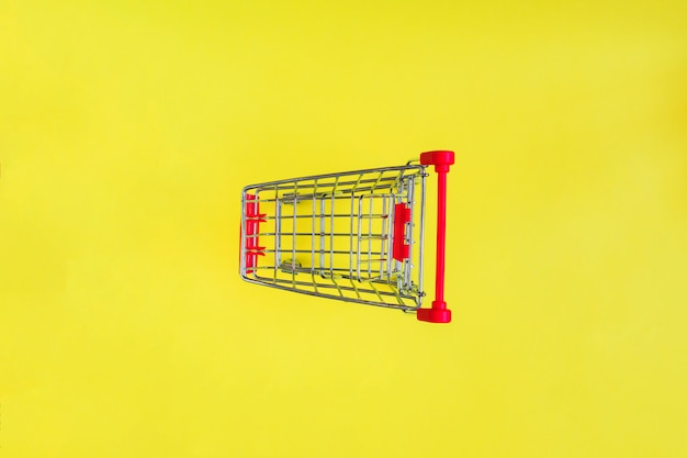 Empty shopping cart on yellow.