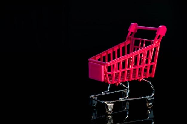 Empty shopping trolley on black, mirror background