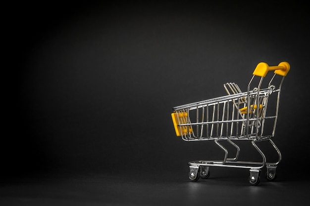 Empty shopping trolley on dark toned background with some copy space