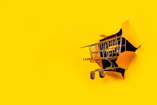 노란색 찢어진 구멍에 빈 쇼핑 트롤리
