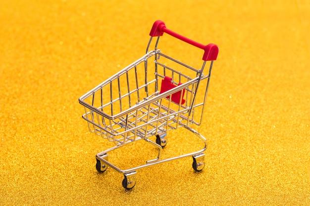 金色の輝く背景の空のショッピングトロリー。製品のバスケットを購入します。