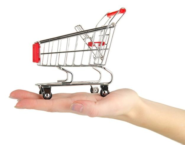 白で隔離される女性の手で空のショッピング カート