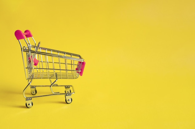 Empty shopping trolley with pink handle on yellow . online shopping . a form of electronic commerce.