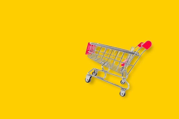 Empty shopping trolley on yellow background. concept of sale and buy in mall market shop. copy space