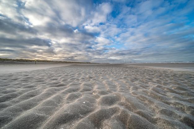 Пустой берег под голубым облачным небом
