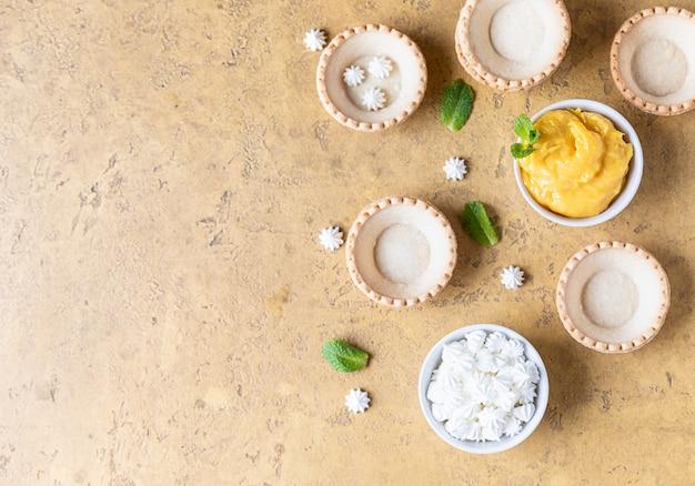 Empty shortbread tartlets, lemon curd, mini meringues and mint on concrete surface