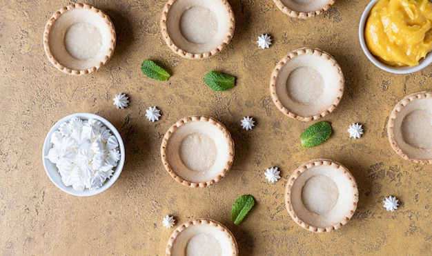 Empty shortbread tartlets lemon curd mini meringues and mint process making dessert