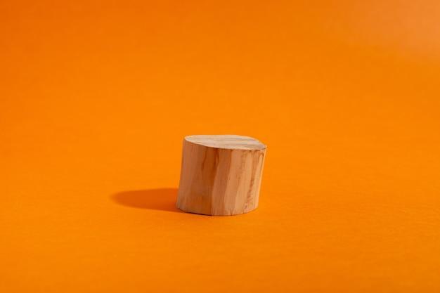 기하학적 형태의 주황색 장면에 있는 나무 원형 연단의 빈 쇼케이스