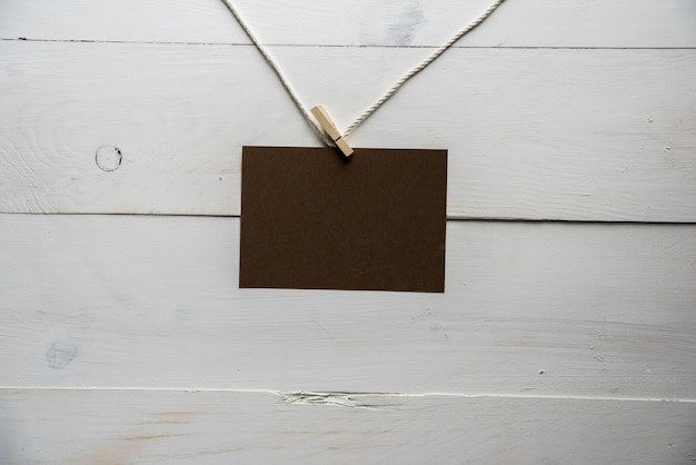 Empty sign attached to a rope with a white wooden wall