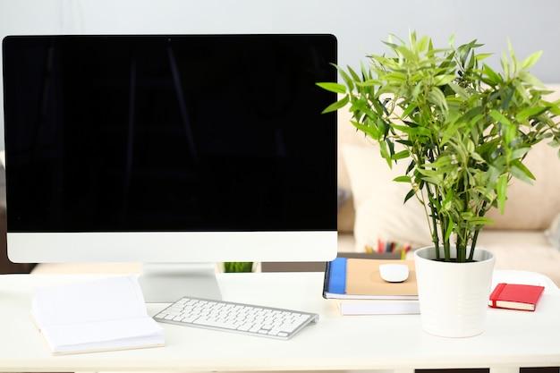 Пустой серебряный компьютер на рабочем столе с диваном