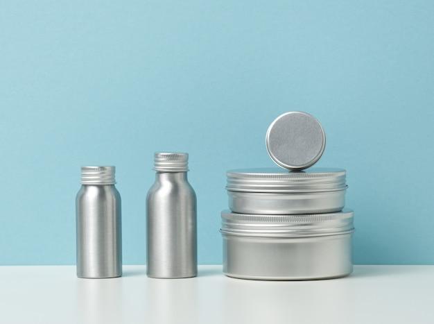 흰색 테이블, 파란색 배경에 화장품을 위한 빈 은색 금속 병. 크림, 젤, 혈청, 광고 및 제품 판촉용 포장. 조롱