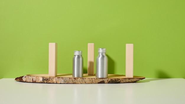 흰색 테이블, 녹색 배경에 화장품을 위한 빈 은색 금속 병. 크림, 젤, 혈청, 광고 및 제품 판촉용 포장. 조롱