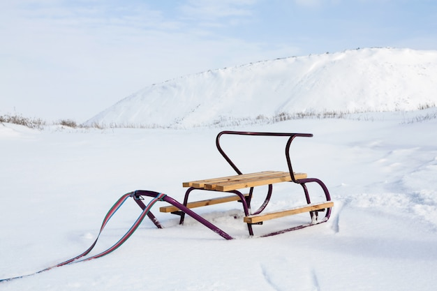 Empty sledge with on the snow on the background of the slagheap