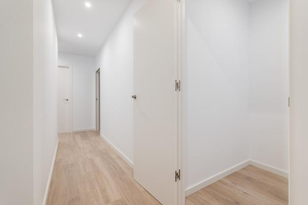 Пустая маленькая комната с белыми стенами и коридором, ведущим в другие комнаты квартиры после ремонта
