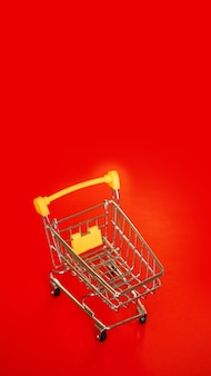 Empty small yellow shopping cart on red background. copy space, place for text. concept sale. vertical photo