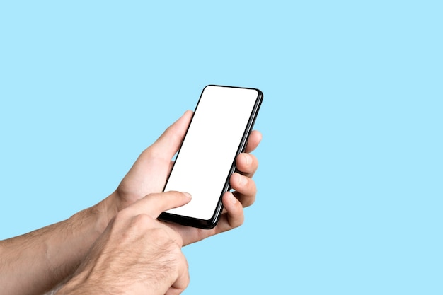 Empty smartphone in hand on colored blue banner background mockup phone with blank screen on minimal...